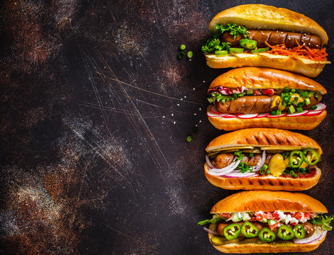 Hot dogs with different toppings on dark background, copy space, top view. Fast food concept.