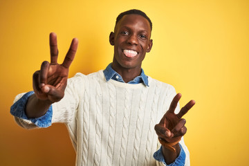 African american man wearing denim shirt and white sweater over isolated yellow background smiling with tongue out showing fingers of both hands doing victory sign. Number two.