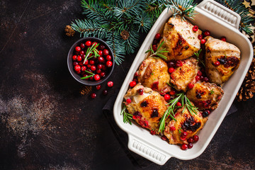 Christmas food. Baked Chicken meat with cranberries and rosemary in the oven dish, dark background, copy space.