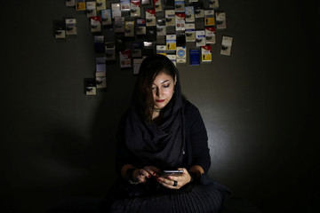 "Shirin Vaezi, an Iranian woman drummer in a Progressive/Djent band named ""Atria"", uses her cellphone at a smoking room in an art department in Tehran"