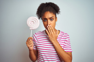 African american teenager woman eating colorful candy over isolated white background cover mouth with hand shocked with shame for mistake, expression of fear, scared in silence, secret concept