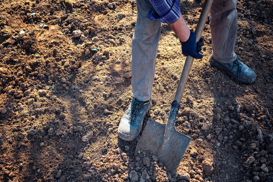 Man digging over earth with a spade