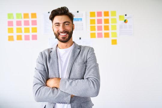 Handsome young startup entrepreneur smiling at camera