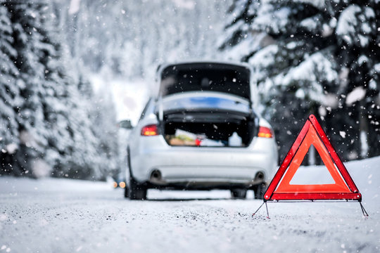 Car trinagle on highway with broken car in winter.