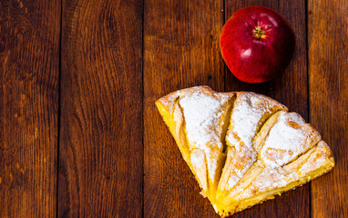 Slices of freshly baked apple pie with sugar powder and red apple on a wooden board. Homemade apple cake.