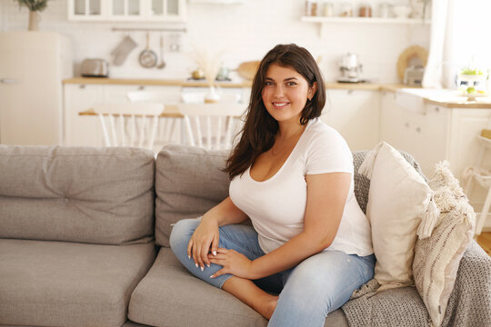 Relaxation, leisure, rest, domesticity and coziness. Beautiful charming young female with chubby cheeks and curvy body sitting on sofa barefooted, keeping one foot on floor, smiling at camera