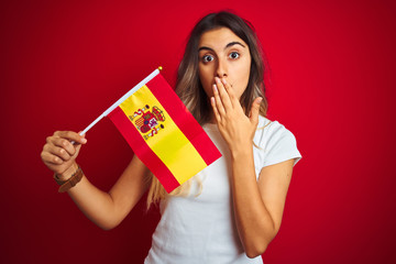 Young beautiful woman holding spanish flag over red isolated background cover mouth with hand shocked with shame for mistake, expression of fear, scared in silence, secret concept