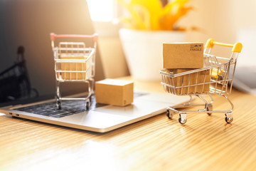 Brown paper boxs in a shopping cart with laptop keyboard on wood table in office background.Easy shopping with finger tips for consumers.Online shopping and delivery service concept.