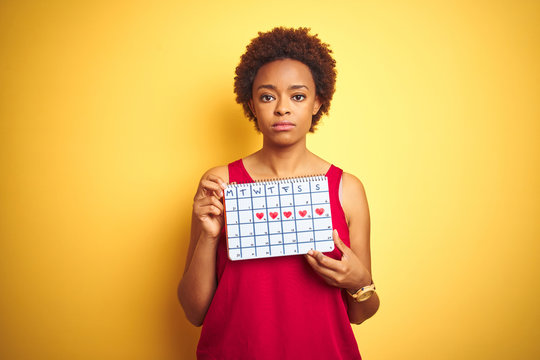 Young african american woman holding menstruation calendar over isolated yellow background with a confident expression on smart face thinking serious