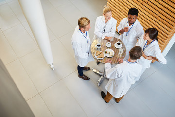 Doctors eat and talk together in the cafeteria