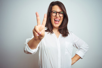 Young beautiful business woman wearing glasses over isolated background smiling with happy face winking at the camera doing victory sign. Number two.