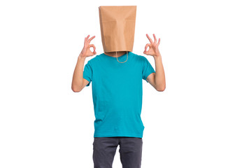 Fototapete - Portrait of teen boy with paper bag over head making Ok gesture, isolated on white background. Child showing okay sign.