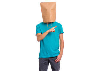 Fototapete - Portrait of teen boy with paper bag over head pointing hands away at copyspace, isolated on white background. Child pointing finger at something.