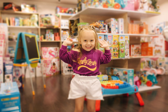 Happy little girl walkning in toy store. Cute girl choose toy. Adorable female in kids mall