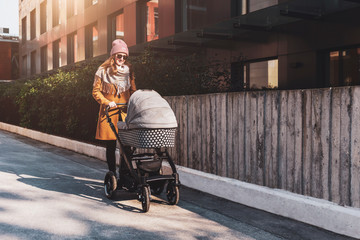 Young woman with baby stroller walking down city streets. Mother with her child in baby carriage having walk through living block.