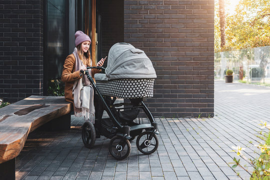 Young woman sitting on bench by multistoried living house with baby stroller. Improved community for parents with children. Apartments in suburbs at affordable price. Woman relaxing in recreation area