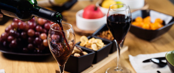Spoed Foto op Canvas Wijn Pouring wine into glass and food background