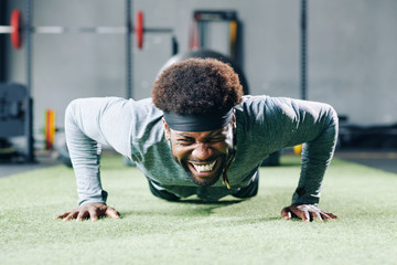 Handsome young Black man struggling with doing push-ups on gym floor