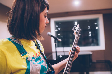 Young woman musician playing electric bass