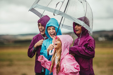 group of children dressed in raincoats and umbrellas not to get wet with the rain are playing happily outdoors