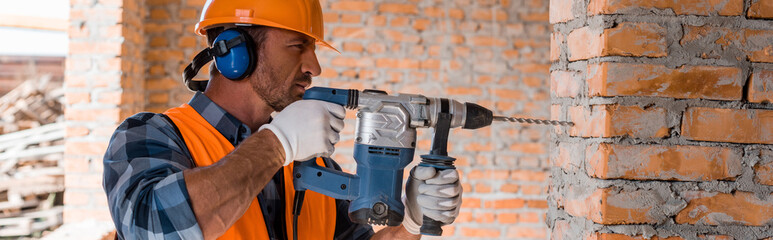 panoramic shot of handsome bearded man using hammer drill near brick wall