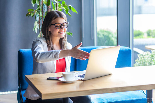 Portrait of happy beautiful stylish young woman in glasses sitting, looking at her laptop screen on video call and giving hand to handshake, toothy smile. indoor studio shot, cafe, office background.