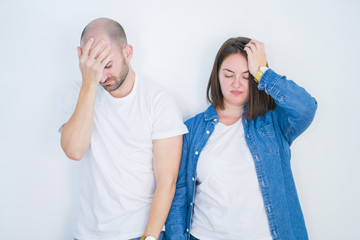 Young couple together over white isolated background suffering from headache desperate and stressed because pain and migraine. Hands on head.
