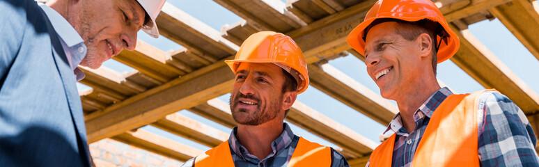 panoramic shot of builders near mature businessman in helmet