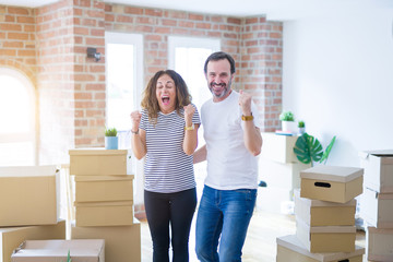 Middle age senior couple moving to a new home with boxes around celebrating surprised and amazed...