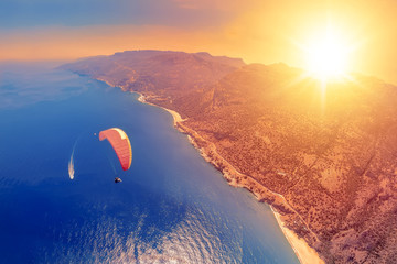 Türaufkleber Koralle Extreme sport. Landscape . Paragliding in the sky. Paraglider tandem flying over the sea with blue water and mountains in bright sunny day. Aerial view of paraglider and Blue Lagoon in Oludeniz, Turke
