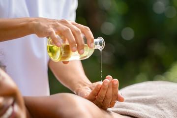 Masseuse hands pouring massage oil