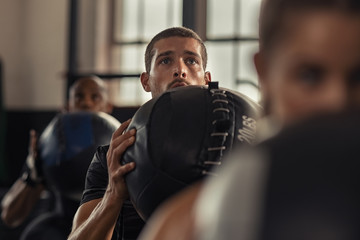 Fitness man doing squat with heavy ball