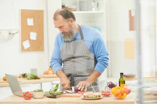 Waist up portrait of bearded senior man cooking dinner at home and looking at laptop screen watching recipe, copy space
