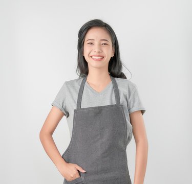 Asian woman in apron and standing and looking forward on gray background. Small business Concept