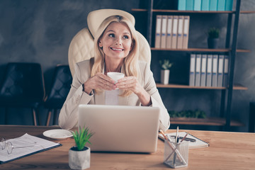 Photo of cheerful positive ceo holding cup of tea with hands sitting in front of computer having...
