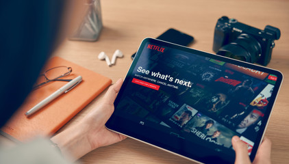 Bangkok, Thailand - October 07, 2019 : women use Netflix app on iPad Pro screen. Netflix is an international leading subscription service for watching TV episodes and movies.