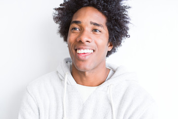 Handsome african american man with afro hair over white background smiling looking side and staring away thinking.