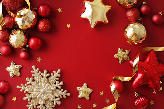 red and gold christmas ornaments on red background. frame background with copy space