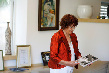 Nadia, widow of Israeli spy Eli Cohen, looks at their wedding photograph during an interview with Reuters in Herzliya, Israel
