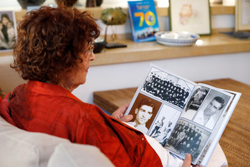 Nadia, widow of Israeli spy Eli Cohen, looks at photographs depicting her late husband during an interview with Reuters in Herzliya, Israel