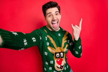 Portrait of funky funny crazy man in deer reindeer sweater make selfie show horned sign scream true...