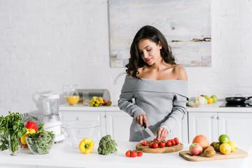 beautiful girl holding knife near cherry tomatoes