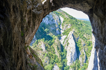 View of the rock walls at Turda gorge (Cheile Turzii) as seen from under an arch in Hili cave, during the via ferrata route that goes through it.