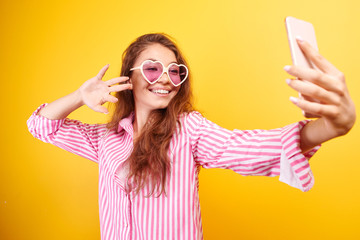 Young funny blogger Asian girlmakes selfie on the phone camera on yellow background, isolated in studio