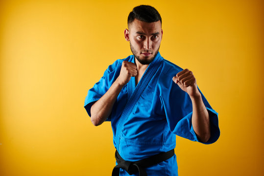 Asian Kazakh karate fighter in kimono uniform is combat on yellow background with copy space isolated