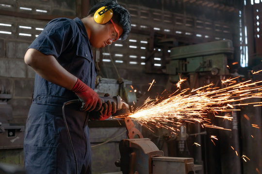 Diverse Asian male engineer operating power tools with sparks in industrial factory