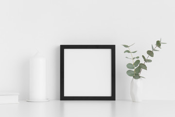 Black square frame mockup with workspace accessories and eucalyptus in a vase on a white table.