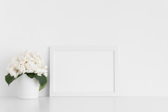 White frame mockup with a hortensia in a pot on a white table.Landscape orientation.