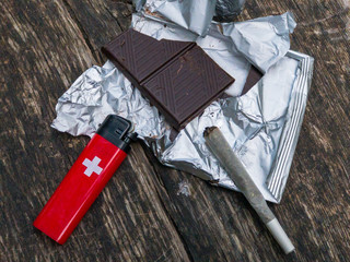 Dark chocolate, swiss lighter and joint with marijuana