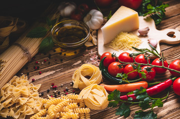 Tasty appetizing italian spaghetti pasta ingredients for kitchen cuisine with tomato, cheese parmesan, olive oil, fettuccine and basil on wooden brown table. Food Italian recipe homemade. Top view Fotomurales